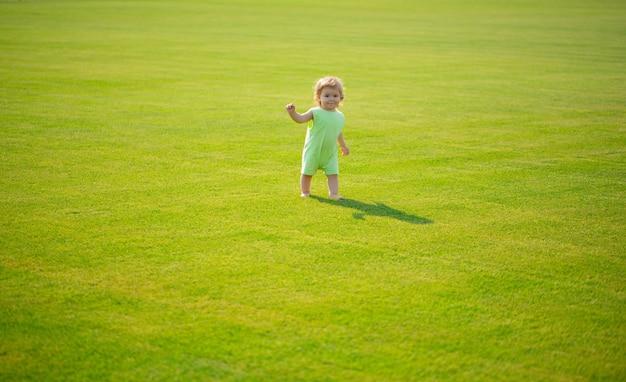 Mignon petit garçon drôle apprenant à ramper étape s'amusant à jouer sur la pelouse dans le jardin