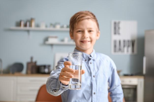 Mignon petit garçon eau potable dans la cuisine
