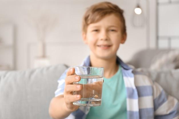 Mignon petit garçon de l'eau potable à la maison