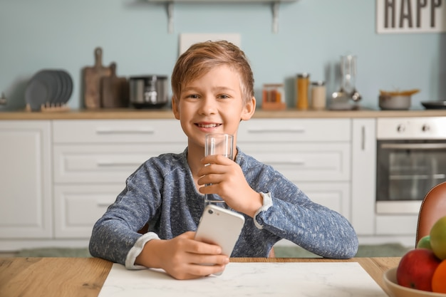 Mignon petit garçon avec de l'eau potable de téléphone portable dans la cuisine