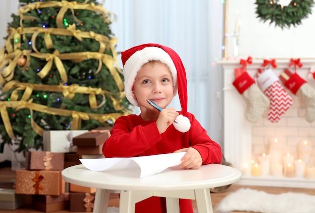 Mignon petit garçon écrit une lettre au père noël à table