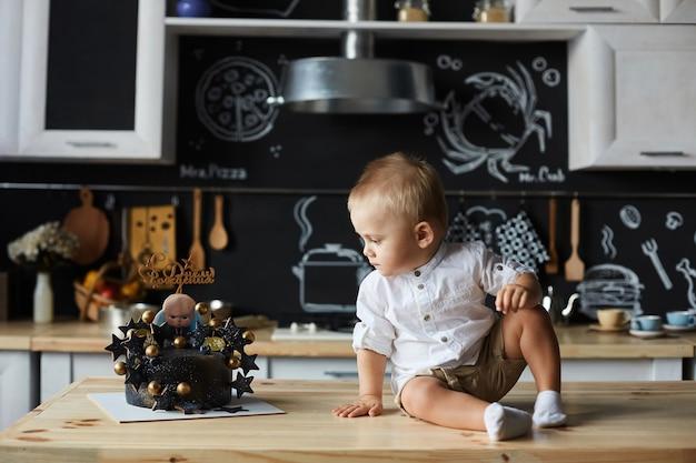 Mignon petit garçon élégant en chemise blanche et short est assis sur la table, regardant un gâteau d'anniversaire et posant à l'intérieur de la cuisine