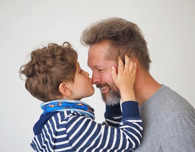 Mignon petit garçon embrasse son père. le père et le fils sont heureux et souriants. journée internationale du baiser.