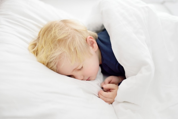 Mignon petit garçon endormi enfant fatigué, faire la sieste dans le lit des parents.