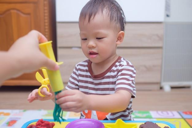 Mignon petit garçon enfant asiatique enfant s'amusant à jouer de la pâte à modeler colorée à la maison