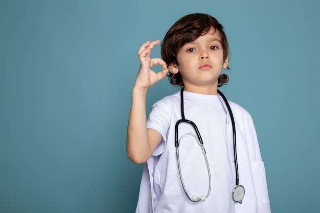 Mignon petit garçon enfant en combinaison médicale blanche montrant signe sur mur bleu