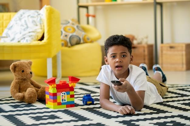 Mignon petit garçon ennuyé et malheureux d'origine africaine poussant le bouton de la télécommande en position couchée devant le téléviseur à la maison