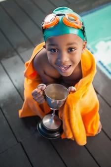 Mignon petit garçon enveloppé dans une serviette avec trophée près de la piscine