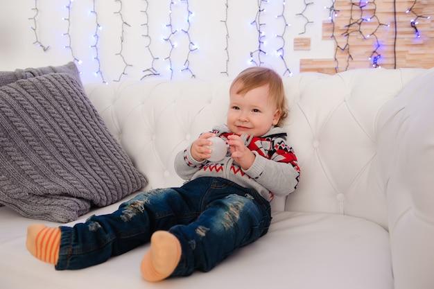 Mignon petit garçon est assis sur le canapé à la maison.