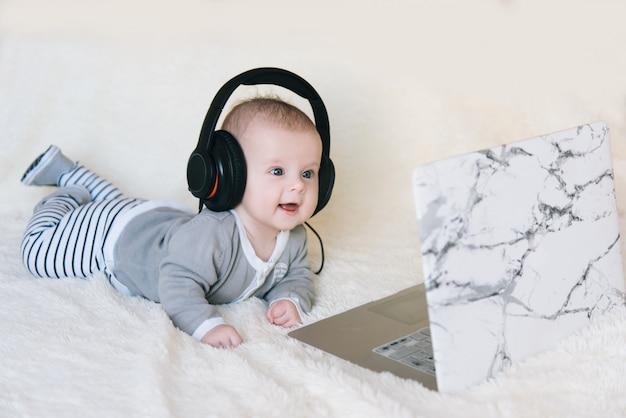 Mignon petit garçon est couché sur le ventre dans les écouteurs et regarde dans un ordinateur portable, mise au point sélective