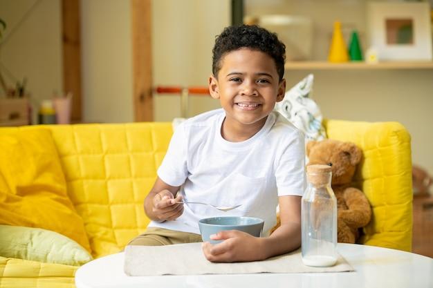 Mignon petit garçon d'ethnie africaine avec un sourire à pleines dents alors qu'il était assis sur le canapé et mangeant des cornflakes avec du lait pour le petit déjeuner