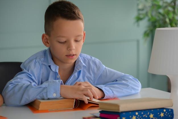 Mignon petit garçon faisant ses devoirs à la maison en ligne