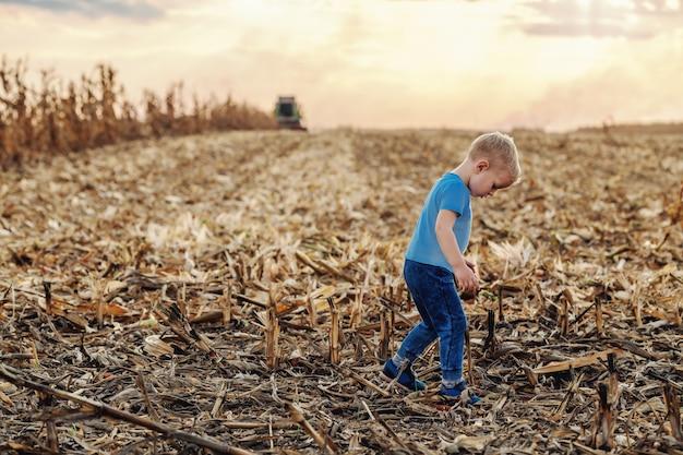 Mignon petit garçon fermier debout sur un champ de maïs et jouer