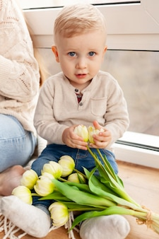Mignon petit garçon avec des fleurs
