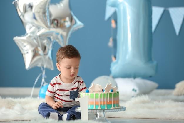Mignon petit garçon avec un gâteau d'anniversaire assis sur un tapis moelleux dans la chambre