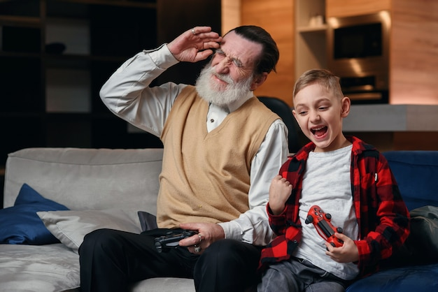 Mignon petit garçon avec grand-père assis sur un canapé et jouer à un jeu vidéo avec une manette de jeu