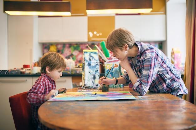 Mignon petit garçon heureux et enseignant dessin en classe d'artiste.