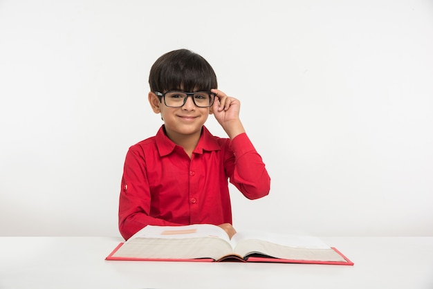 Mignon petit garçon indien ou asiatique tenant ou lisant un livre sur une table d'étude ou sur un sol blanc, isolé sur fond blanc