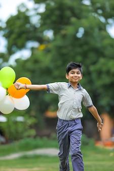 Mignon petit garçon indien avec des ballons tricolores et célébrant l'indépendance ou le jour de la république de l'inde