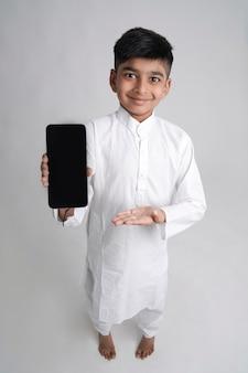 Mignon petit garçon indien montrant l'écran du téléphone intelligent