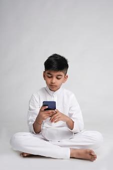 Mignon petit garçon indien utilisant un téléphone intelligent