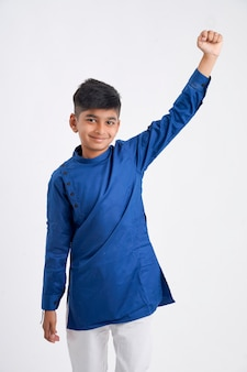 Mignon petit garçon indien en vêtements ethniques et montrant l'expression sur blanc