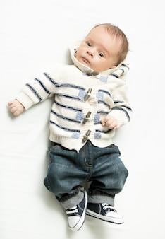 Mignon petit garçon en jeans et pull allongé sur le lit