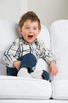 Mignon petit garçon jouant à la maison sur le canapé