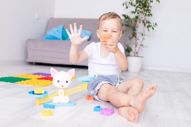 Mignon petit garçon joue avec des échelles à la maison sur le sol et apprend à compter en montrant cinq doigts