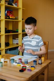 Un mignon petit garçon joue et peint dans sa chambre. loisirs et divertissements. reste à la maison.