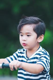 Un mignon petit garçon joue à un scooter dans un parc.