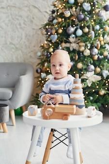 Mignon petit garçon joue avec train en bois jouet, voiture jouet, pyramide et cubes, concept de développement d'apprentissage. développement de la motricité fine des enfants, de l'imagination et de la pensée logique