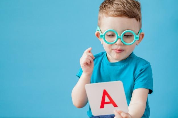 Mignon petit garçon avec lettre sur bleu. l'enfant apprend les lettres.