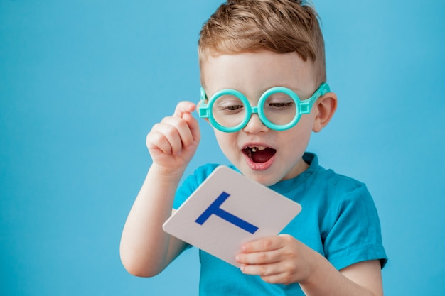 Mignon petit garçon avec lettre sur fond. l'enfant apprend des lettres.