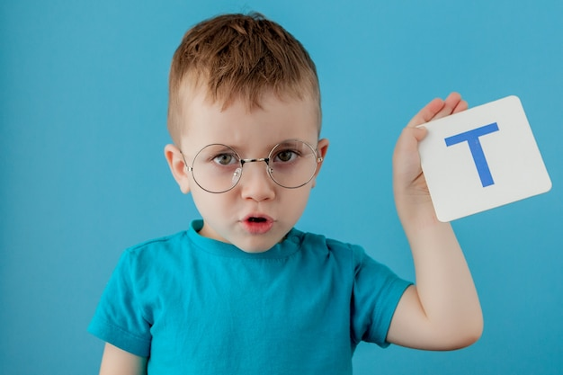 Mignon petit garçon avec une lettre sur le mur bleu. enfant apprenant une lettre. alphabet