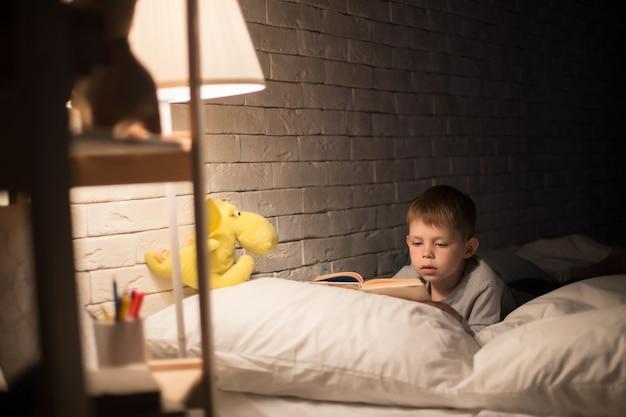 Mignon petit garçon lisant dans son lit