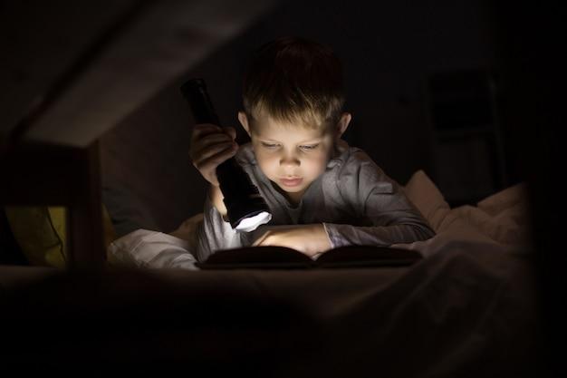 Mignon petit garçon lisant avec lampe de poche