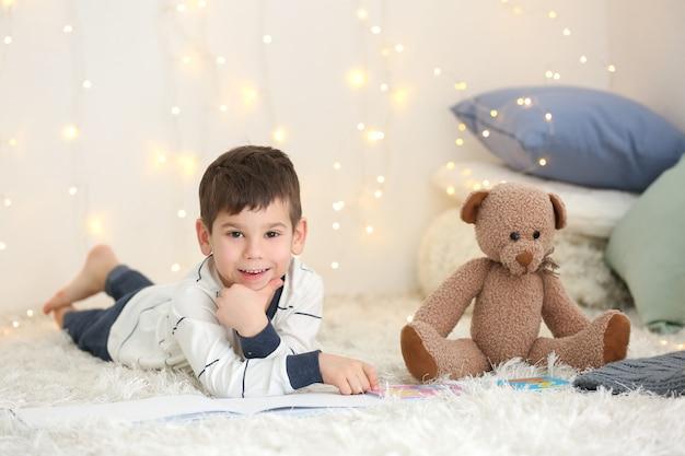 Mignon petit garçon avec un livre de lecture d'ours en peluche à la maison