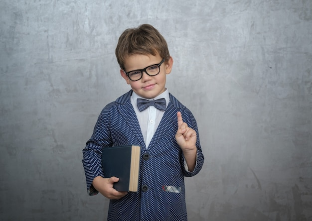 Mignon petit garçon à lunettes noires, veste élégante avec un papillon et un livre dans ses mains