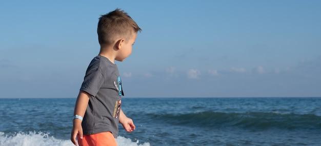 Mignon petit garçon marchant sur la plage dans les vagues mousseuses de la mer.