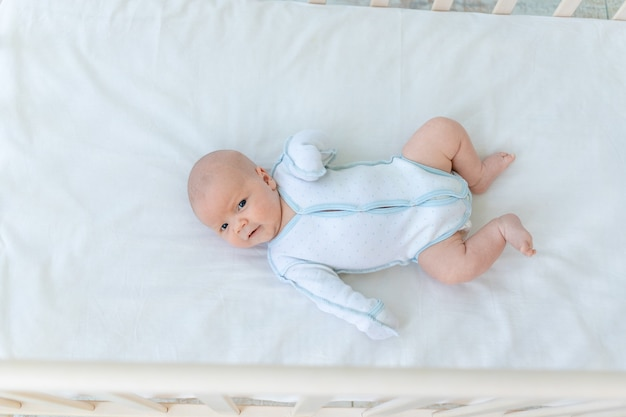 Mignon petit garçon nouveau-né allongé à l'arrière du berceau sur le lit en coton à la maison avant d'aller au lit, semaine de bébé, le concept de naissance et de petite enfance, vue de dessus.