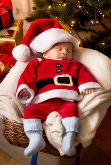 Mignon petit garçon nouveau-né en costume de père noël dormant dans le panier