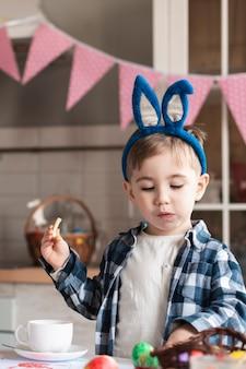 Mignon petit garçon avec des oreilles de lapin ayant une collation