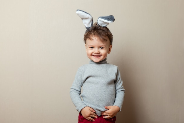 Mignon petit garçon avec des oreilles de lapin sur fond gris