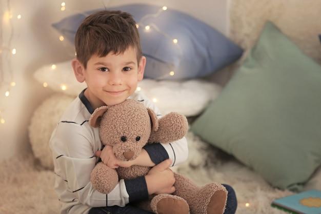 Mignon petit garçon avec ours en peluche à la maison