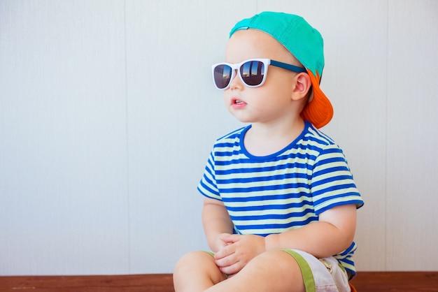 Mignon petit garçon portant casquette et lunettes de soleil sur blanc