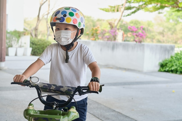 Mignon petit garçon portant un masque médical protecteur et un casque de sécurité faisant du vélo dans le parc