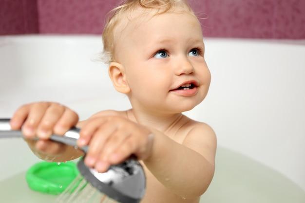 Mignon petit garçon prenant une douche dans la salle de bain