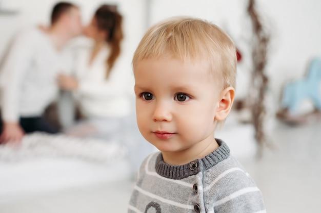 Mignon petit garçon en pull gris debout en studio et à la recherche de suite tandis que les jeunes parents amoureux étreignant et s'embrassant derrière