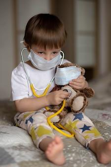 Mignon petit garçon en pyjama à l'aide d'un stéthoscope sur un ours en peluche